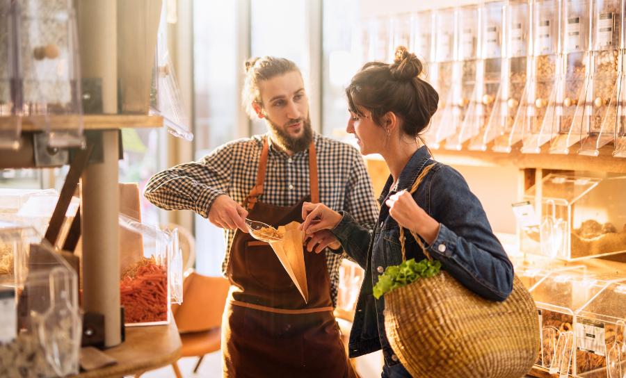 Junger Mann bedient junge Frau in einem Laden - Einen eigenen Laden eröffnen will geplant sein