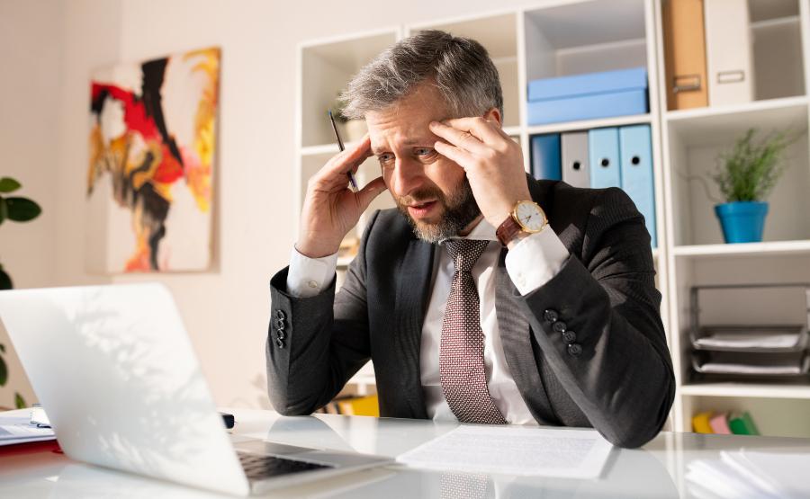 Mann sitzt grübelnd am Computer - wann gibt es Anspruch auf ein Zwischenzeugnis?