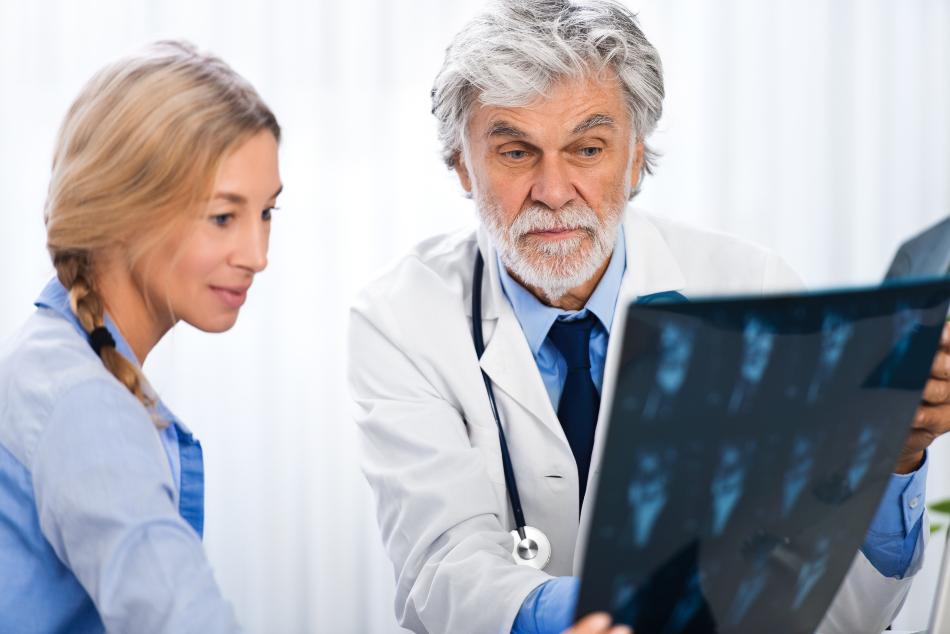 Arzt analysiert Röntgen-Aufnahmen einer Patientin - Krankenversicherung für Selbstständige