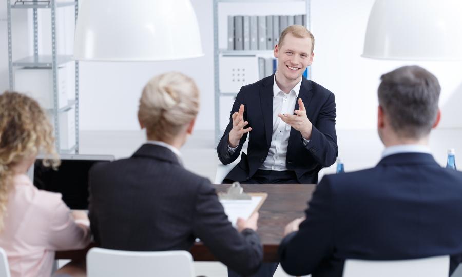 Junger Mann präsentiert sich vor Geldgebern - Investoren finden mit professionellem Auftreten