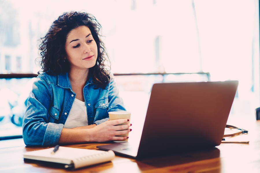 Junge Frau liest am Laptop - die perfekte Bewerbungsmappe