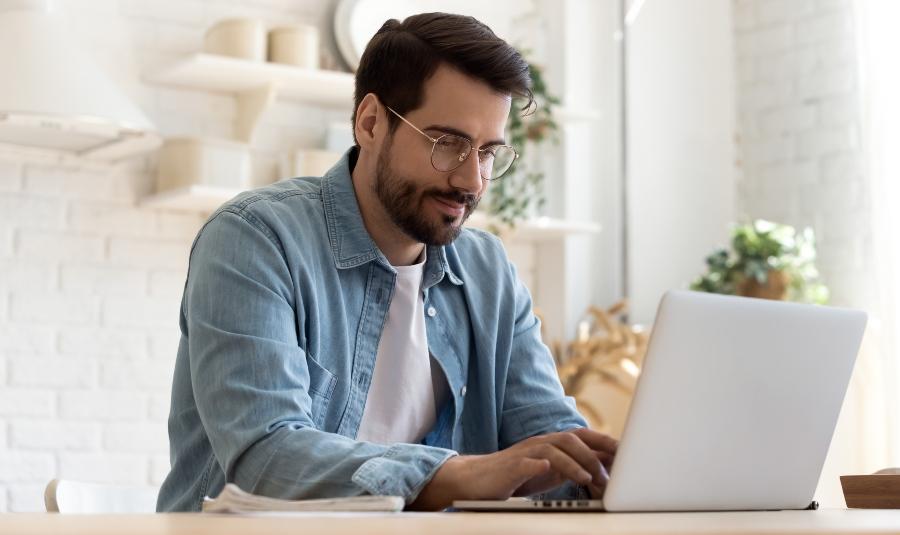 Junger Mann schreibt am Laptop - die perfekte Bewerbungsmappe
