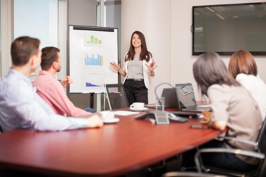 Junge Frau präsentiert vor Investoren ihren Business-Plan