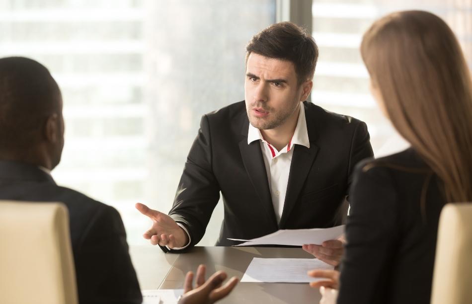 Junger Mann in agitiertem Gespräch mit 2 weiteren Personen - Assessment Center Situation