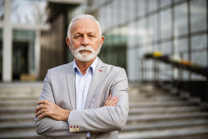 Autoritär wirkender älterer Herr in Anzug - Führungsstile in Unternehmen