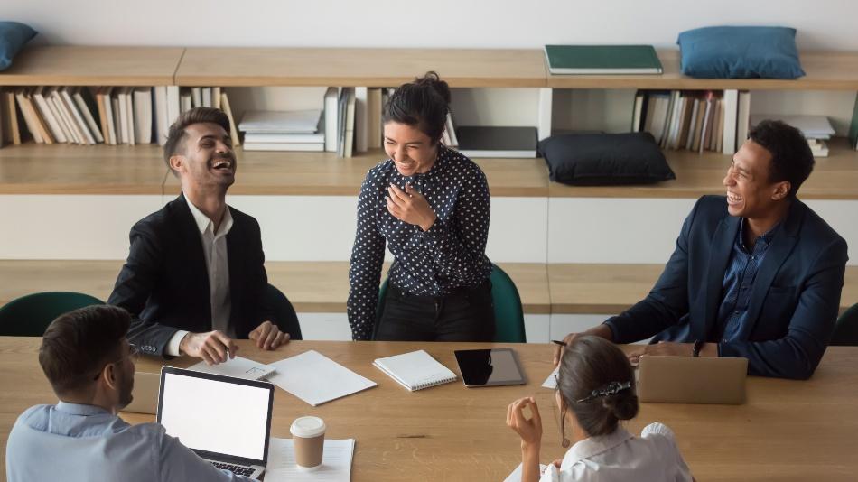 Runde junger Leute in Arbeitsumgebung unterhalten sich fröhlich - Führungsstile in Unternehmen