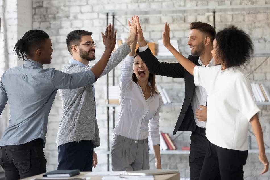 """Gruppe junger Mitarbeiter macht """"High Five"""""""