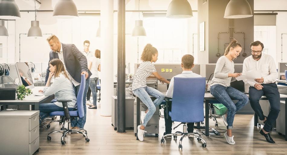 Büroraum mit mehreren Gruppen und Gesprächsrunden -Führungsstile in Unternehmen