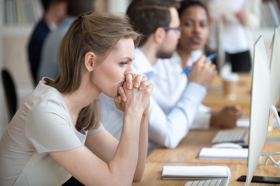 Junge Frau am Arbeitsplatz wirkt genervt