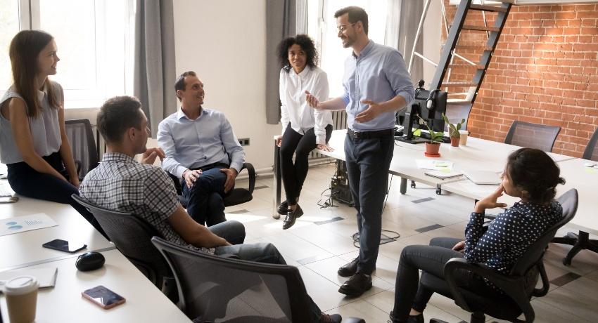 Junge Führungskraft spricht zu Mitarbeitern - Führungsstile in Unternehmen