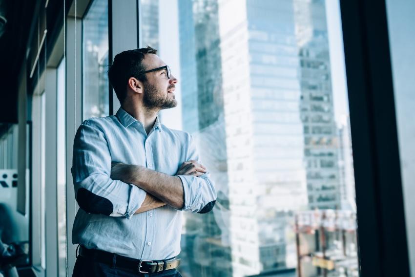 Junger Mann schaut aus dem Fenster auf Bankgebäude und denkt nach - Business Development