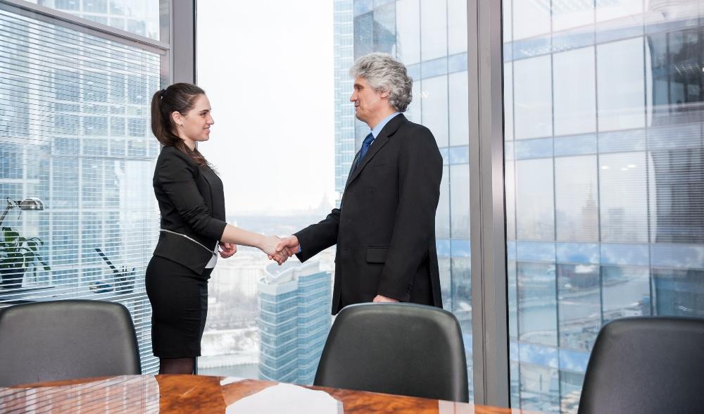 Boss schüttelt die Hand einer jungen Angestellten / Praktikantin
