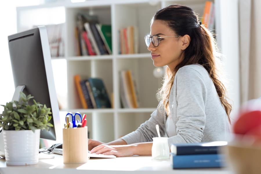 Junge Frau sitzt am Computer - vielleicht recherchiert sie für eine Initiativbewerbung