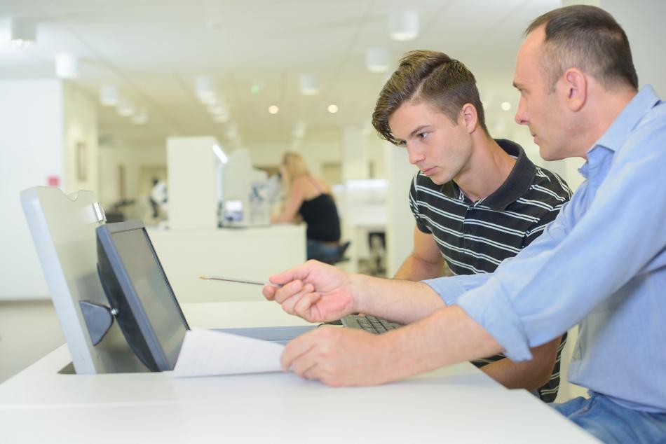Praktikant wird von Angestelltem am Laptop eingewiesen - Praktikanten beschäftigen