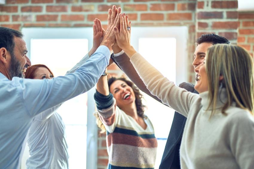 """Gruppe von Angestellten macht """"High-Five - Betriebsklima verbessern ist jederzeit eine Aufgabe"""