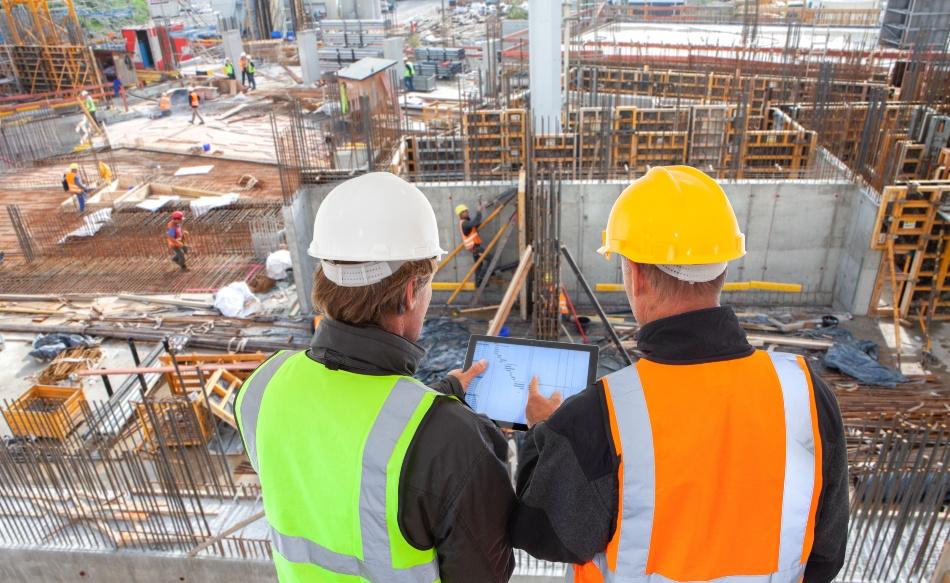 Zwei Architekten/Handwerker begutachten eine große Baustelle aus erhöter Position