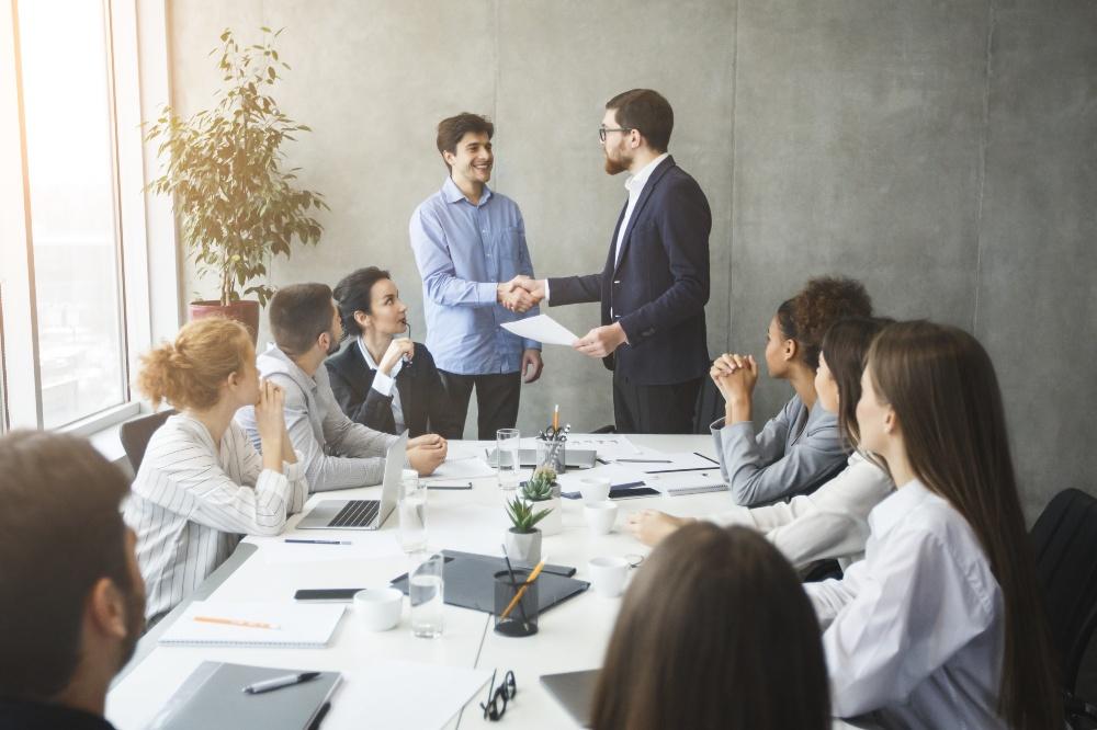 Boss beglückwünscht Angestellten vor einigen Kollegen