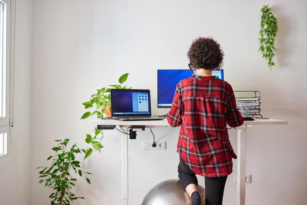 Junge Frau an einem hochgefahrenen Schreibtisch und Sitzball