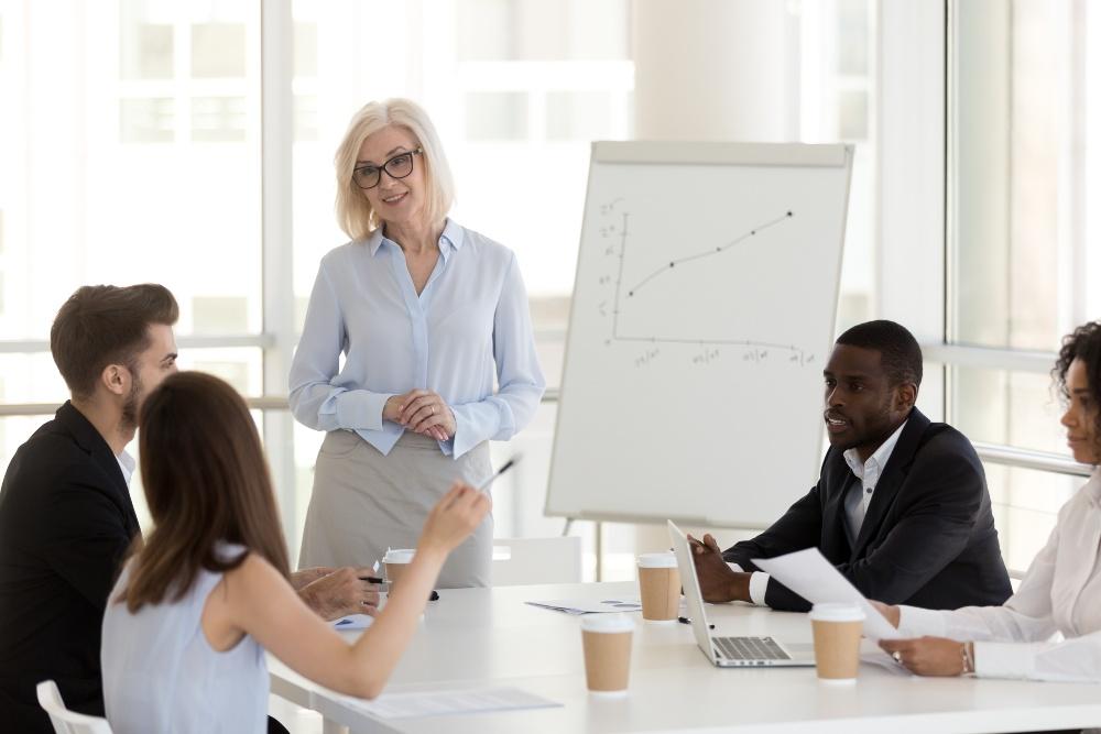 Frau hält gegenüber Kollegen/Mitarbeitern einen Vortrag