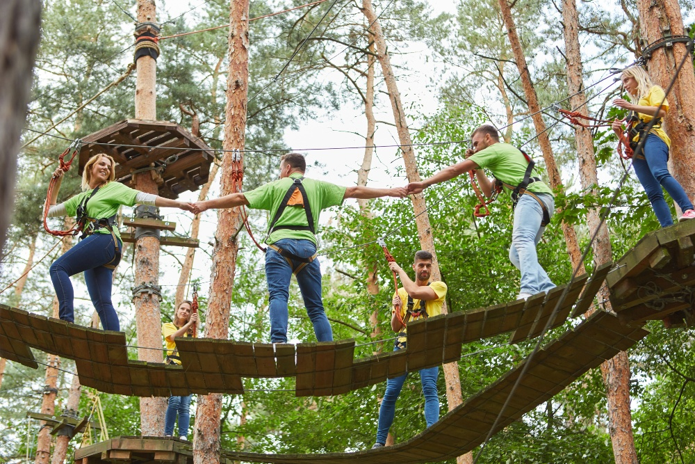 Gruppe Angestellter macht Vertrauensbildende Maßnahme beim Klettern im Wald