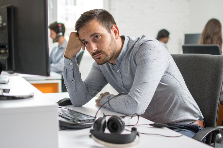 Junger Mann am Arbeitsplatz macht einen unzufriedenen Eindruck - Betriebsklima verbessern ist langwierig