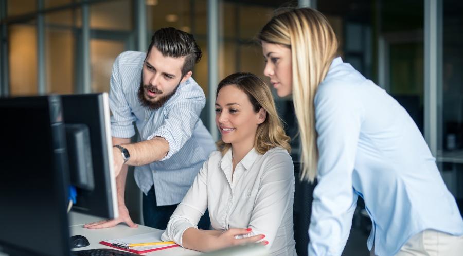 Junge Mitarbeiter zusammen vor Computer - Betriebsklima verbessern