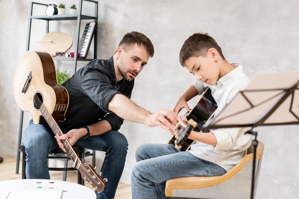 Gitarrenlehrer hilft jungem Schüler